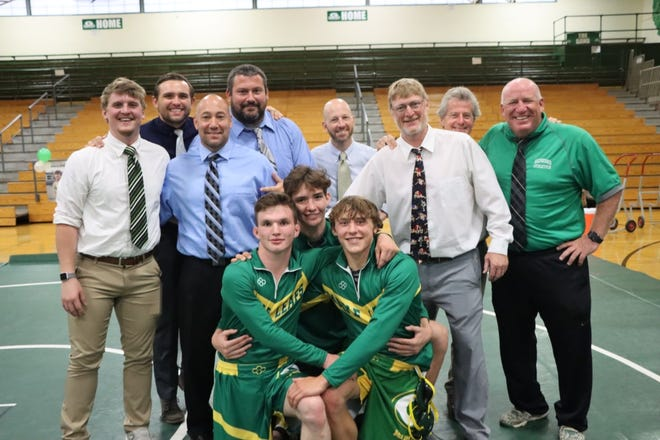 Geneseo senior wrestlers, Logan Tuggle, Clay DeBaillie, and Bruce Moore pose for a picture with the Geneseo wrestling coaches. All three seniors won with a pin on senior night held May 26.