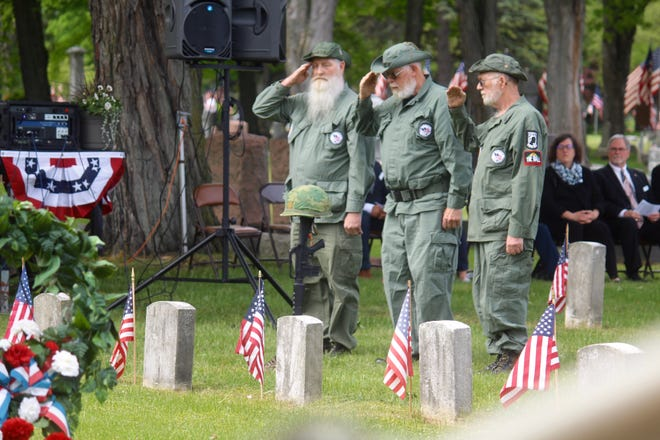 Members of the Vietnam Veterans of America Chapter 73 salute a field cross during Holland's Memorial Day ceremony on Monday, May 31, 2021, at Pilgrim Home Cemetery in Holland, Mich.