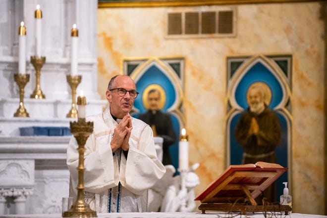 Monsignor Brian Brownsey delivers a homily during a Gold Star Mass at St. Mark Catholic Church in Peoria on Monday, May 31, 2021. During the service, the parish rededicated a plaque honoring the nine men from the parish who died in World War II.