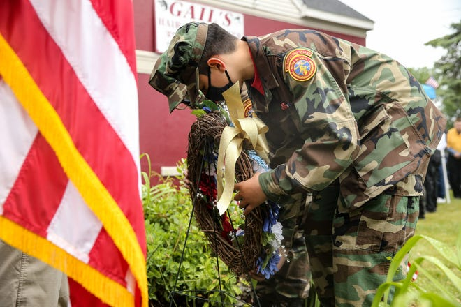 Matthew Alencar, foreground, and Rhennan Monteiro, of the Blackstone Valley Young Marines, place a wreath during a Memorial Day ceremony honoring those who died while serving our country at Calzone Park in Milford on May 31, 2021.