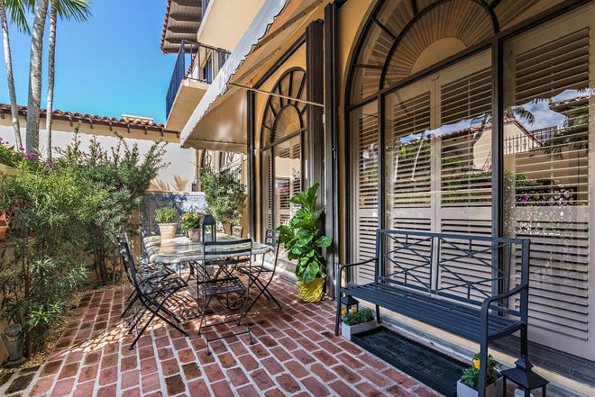 With doors opening into the living area, the brick-paved dining terrace is at the front of the condominium by the courtyard.