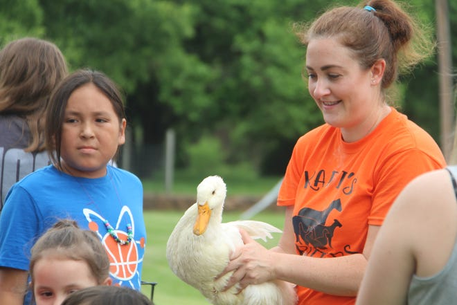 """Kadie Griffin, of Kadie's Kritters out of Terlton, displays """"Donald"""" the duck to children on Wednesday, May 26, outside the Pawhuska Public Library. Griffin brought a duck, a chicken, several rabbits, goats and miniature horses to provide a petting zoo activity for the kids during the first week of the library's Summer Reading Program. Some of the children participating insisted the duck's name should be """"Aflac."""""""