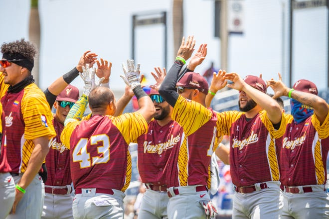 The Venezuela baseball team celebrates its 6-5 victory over Cuba Monday at Ballpark of the Palm Beaches.