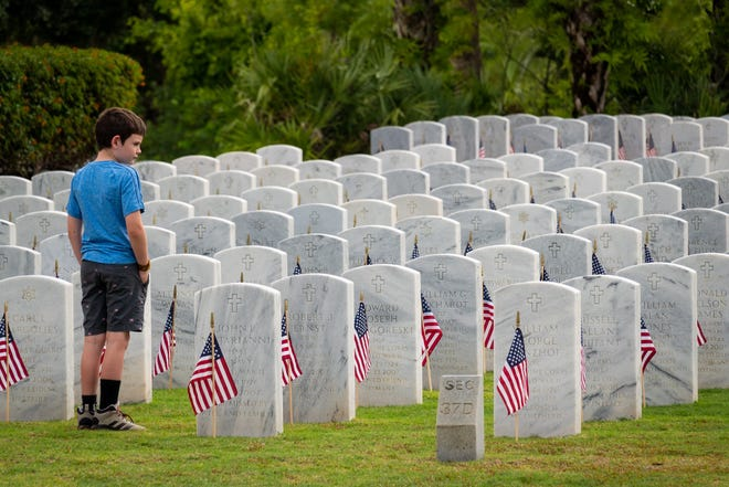Trent Harvey, 8, of Lake Worth, looks over a group of headstones following a Memorial Day ceremony at the South Florida National Cemetery in Lake Worth, Florida on May 31, 2021.   RICHARD GRAULICH/PALM BEACH POST