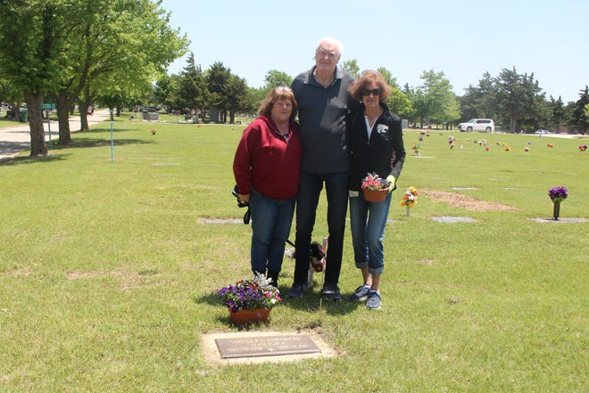 Janna Heberman (left) is joined by Lee and Gail Ochs at the grave of shared veteran Stanley Burnette on Saturday at Pratt's Greenlawn Cemetery.