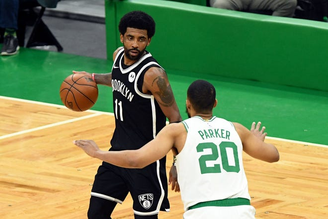 Brooklyn Nets guard Kyrie Irving (left) dribbles the ball in front of Boston Celtics forward Jabari Parker during the second half of Game 4 in the first round of the 2021 NBA Playoffs at TD Garden on Sunday.