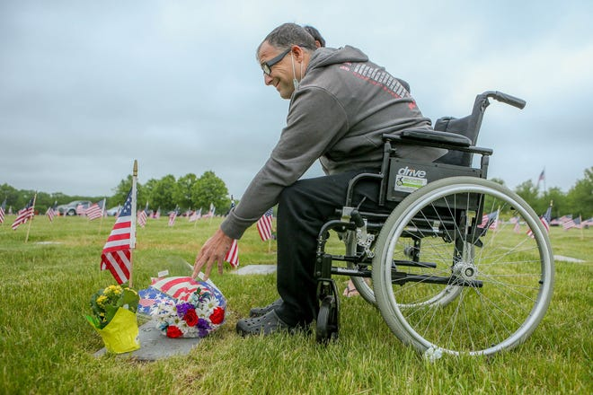 Carl Beauchamp Jr. lays flowers down on his father's gravestone at the Rhode Island Veterans Memorial Cemetery in Exeter. His father was born in 1938 and served in the U.S. Navy.