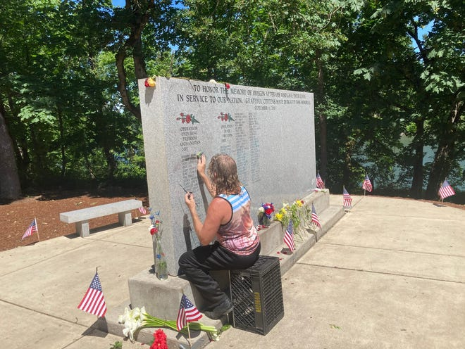 Jimmy Lynch adds black paint Memorial Day morning to the lettering of the Wall of Honor Memorial in Skinner Butte Park.