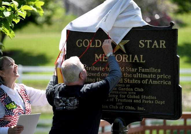 Lake Cable Garden Club President Julie Edwards, left, and Larry Kessler, whose sonU.S. Army Staff Sgt.KevinKessler was killed in Afghanistan in 2010, unveil the Gold Star Families Memorial plaque Monday at Jackson North Park in Jackson Township.
