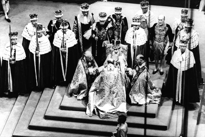 Britain's Queen Elizabeth II, seated on the throne, receives the fealty of the archbishop of Canterbury, center with back to camera, the bishop of Durham, left, and the bishop of Bath and Wells, during her coronation in Westminster Abbey on June 2, 1953.