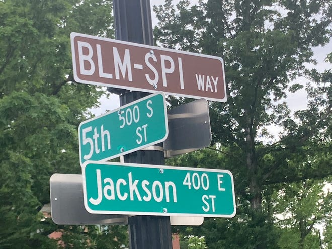 A sign for BLM-SPI Way at Fifth and Jackson streets, with the Governor's Mansion in the background.