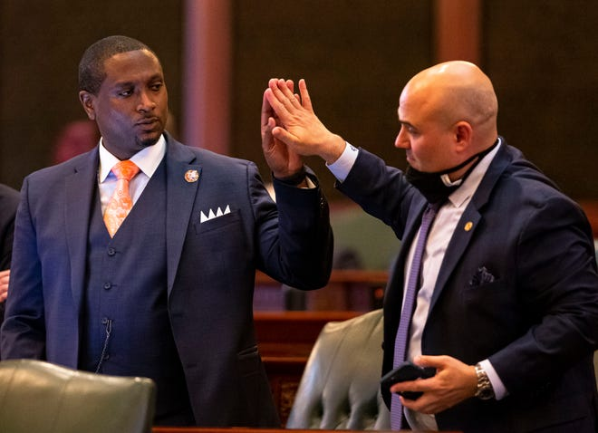 State Rep. Maurice West, D-Rockford, left, gets a high-five Monday from state Rep. Jonathan Carroll, D-Northbrook, after passage of Senate Bill 825, an election omnibus bill which would change Illinois' 2022 primary election from March 15 to June 28 along with voter access changes, on the floor of the Illinois House of Representatives at the Capitol. [Justin L. Fowler/The State Journal-Register]