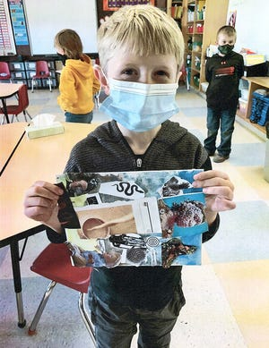 A child shows off his art work as part of a Liberty Arts project.
