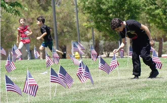 A boy straightens an American flag during the Memorial Day ceremony at Civic Center Park Amphitheater in Apple Valley on Monday, May 31, 2021.