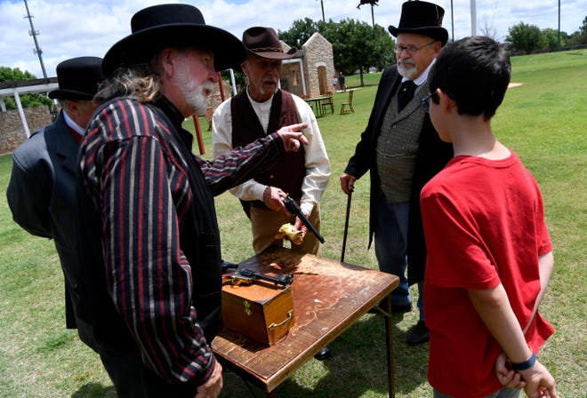 Jason Beckling, 10, listens to the re-enactors of the 1884 Pine Street shootout describe the replica weapons they performed with at Frontier Texas! on Saturday.