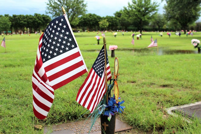 Flags placed at gravesites flutters in a light breeze Monday morning at Elmwood Memorial Park, where portions at the cemetery were under water after heavy thunderstorms passed through the area. A Memorial Day event there was canceled, as was one at Texas State Veterans Cemetery at Abilene at 11 a.m.