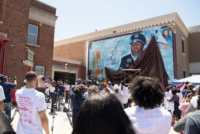 Community members watch during the unveiling of a mural at the Detroit fire station at 7 Mile Rd. near John R Rd. on May 30, 2021. The mural memorializes Detroit's victims of the Covid-19 pandemic.