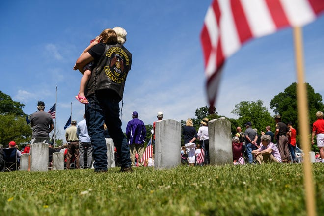 Harley Young, 4, rests on her grandfather James Asher's shoulder as they listen to retired Navy Captain Dr. Mark Browning give a keynote speech during the annual Memorial Day service held at the Veterans Plaza inside Oak Hill Cemetery and Arboretum in Evansville, Ind., Monday morning, May 31, 2021. The event was hosted by the American Legion Funkhouser Post No. 8 to honor soldiers killed in active duty and local veterans who have died over the past year.