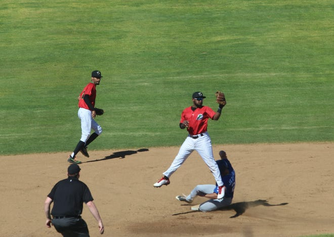 Ogden's Frankie Jezioro slides in safely with a stolen base as the Voyagers' Mike Howard come down with the throw in the second inning of Sunday's Pioneer League game at Centene Stadium.