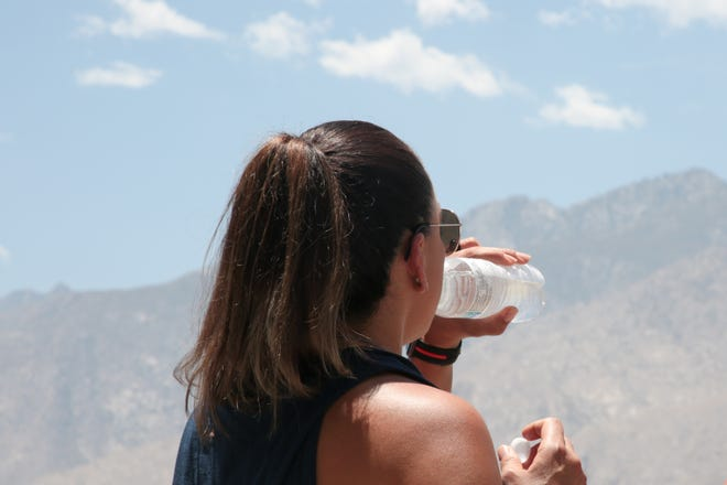 A woman drinks water during the Memorial Day flower drop ceremony at Palm Springs Air Museum on Monday, May 31, 2021, in Palm Springs, Calif.
