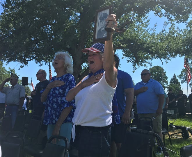 Rebecca Anenson holds up a picture of her father, who served 32 years in the Air Force, as says the Pledge of Allegiance at the Memorial Day ceremony in Anderson on Monday, May 31, 2021.