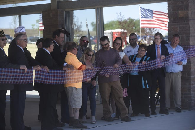 Erin Brown, cemetery director, cuts the ribbon on the South Dakota Veterans Cemetery