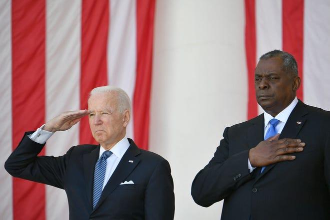 President Joe Biden salutes next to Defense Secretary Lloyd Austin at the 153rd National Memorial Day Observance at  Arlington National Cemetery on May 31, 2021.