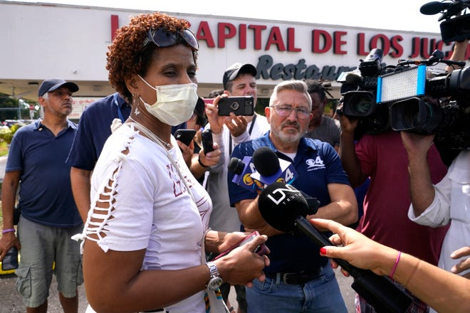 Angelica Green talks with the news media near the scene of a shooting outside a banquet hall near Hialeah, Fla., Sunday, May 30, 2021. Two people died and an estimated 20 to 25 people were injured in a shooting outside a banquet hall in South Florida, police said. The gunfire erupted early Sunday at the El Mula Banquet Hall in northwest Miami-Dade County, near Hialeah, police told news outlets. Green said her son and nephew were injured in the shooting.