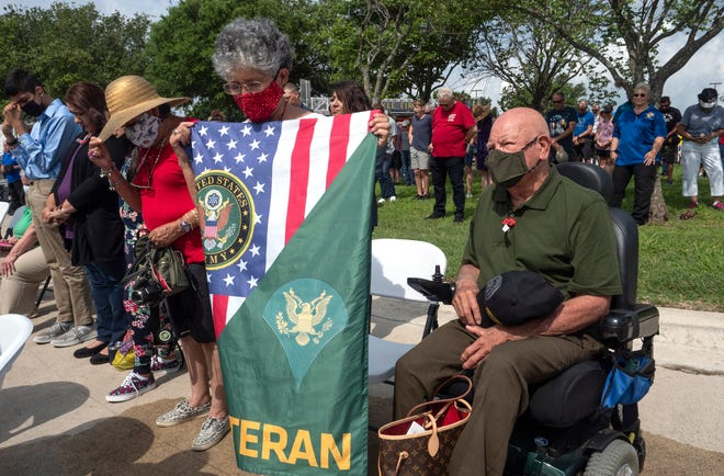 Angelita Tobias, holds a flag in honor of veterans as her husband, Army vet Rosalio Tobias of Kyle, sits next to her during the closing prayer at the groundbreaking for the Heroes Memorial Park on May 31 in Kyle.