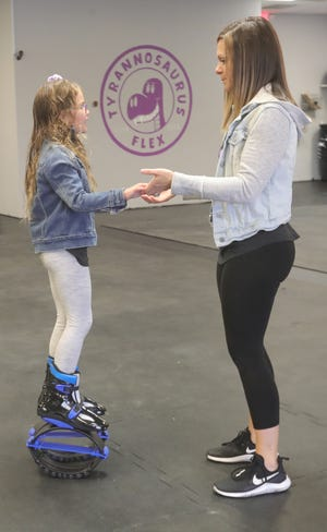 Emma Blake gets help from her mom, Kristin, while balancing on a pair of kangaroo shoes during the grand opening Saturday of Tyrannosaurus Flex Fitness in Stow.