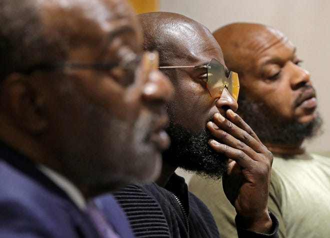 Kenny Walker, center, listens as his attorney Ed Gilbert, front, speaks on behalf of the family during a press conference in Akron on Tuesday. The family plans to file a lawsuit against Canton City School District because they say the football coaches forced their son to eat pork, which is against his religion, as punishment for missing a voluntary practice.