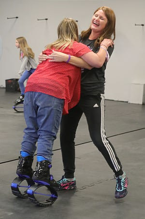 Tyrannosaurus Flex Fitness owner Kellie Dziemianzuk helps first-time kangaroo shoe user Ashley Bach with her balance Saturday in Stow.
