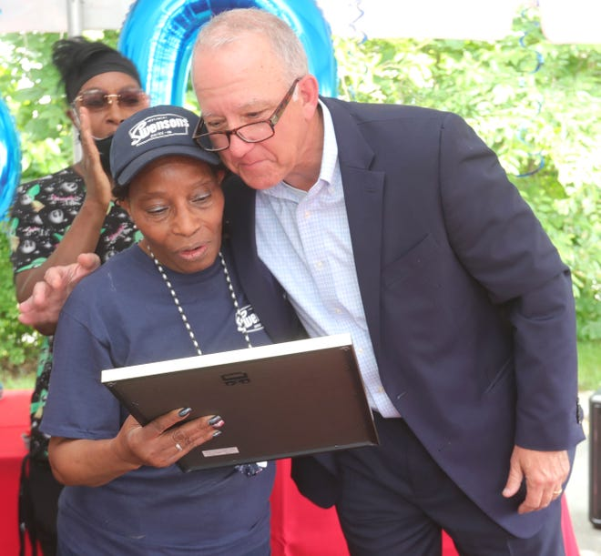 Swensons 50-year employee Ernestine Stallworth reads a proclamation with Akron Mayor Dan Horrigan at a parking lot party in her honor Tuesday in Akron.