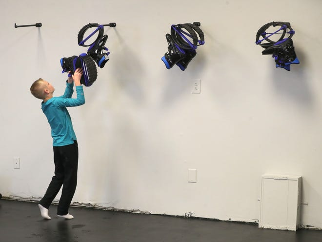Logan Swan puts away his kangaroo shoes after taking them out for a test run during the grand opening Saturday of Tyrannosaurus Flex Fitness in Stow.