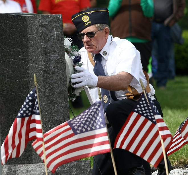 Tom Mather from George T. Worth American Legion Post 574 places a wreath at the veterans memorial Monday, May 31, 2021, during a Memorial Day service at Highland Memorial Cemetery.