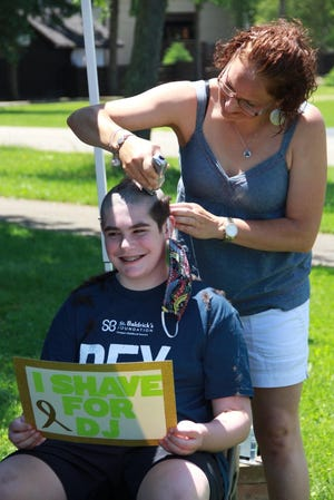 Gavin Clay smiles for a camera as he gets his head shaved in June 2020 during a virtual St. Baldrick's event. Clay participated in the event in memory of DJ Patterson, a Louisville classmate of Clay's.