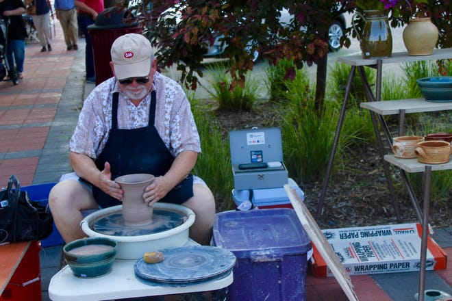 Potter Greg Lamont creates a clay vase during the Art Walk in downtown Ames in June 2017.