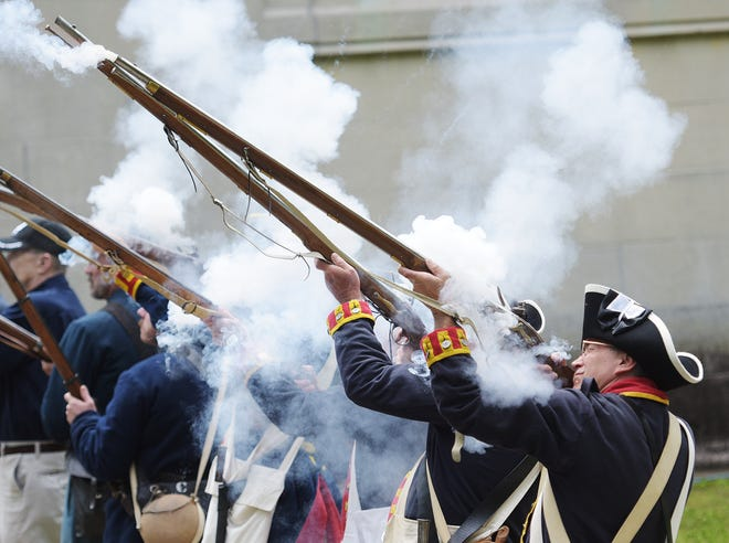 American Revolution reenactors participate in a volley fire salute during the Memorial Day program, Monday at the Beaver Cemetery.