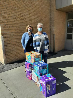 Kiwanis member Diane Seddon stands by ECFE's Gina Gunderson and the display of pullups donated to preschoolers