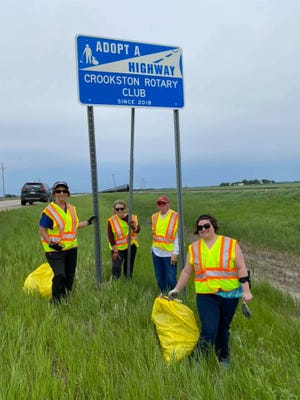 Rotary members clean up their adopted ditch on Highway 75 South