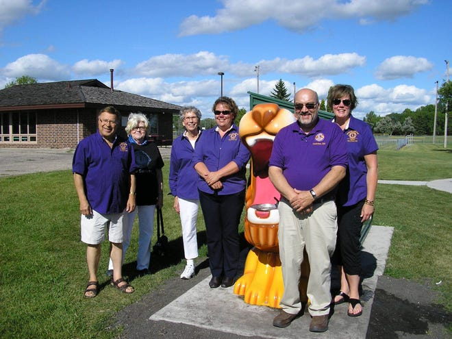 Lions members pose near their Lion water fountain installed a few years ago near Crookston Splash Park