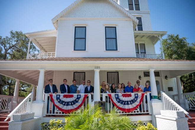 Distinguished guests gather on the newly rennovated porch for the grand re-opening of the Mote Morris House in Leesburg on Tuesday. [Cindy Peterson/Correspondent]