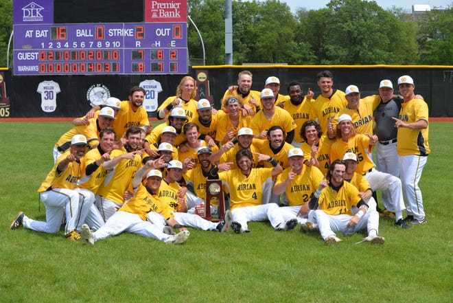 The Adrian College baseball team poses around the NCAA Division III regional championship trophy after beating Wisconsin-Whitewater Monday, 8-7, in 10 innings. (Photo courtesy Mike Prang/Adrian College athletics)