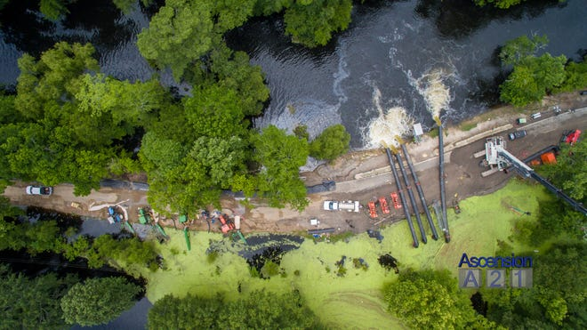 An aerial photo shows Ascension Parish personnel working to facilitate drainage of flood water.