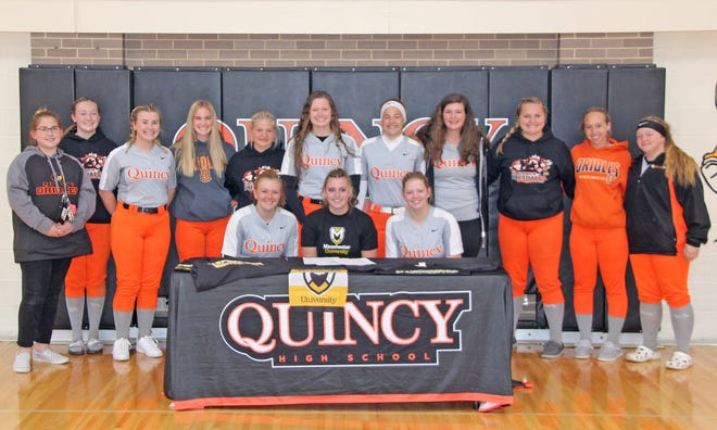 Quincy's Morgan Michael (center) along with her entire team, signed her letter of intent to play softball at Manchester University