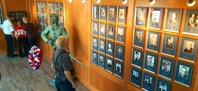 Visitors look at the newly renovated memorial wall, kiosk and soldier statue inside the Daniel Goho American Legion Post after services on Memorial Day.