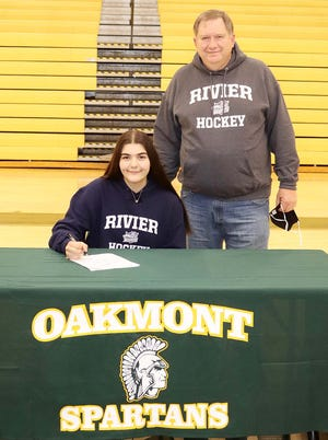 Oakmont senior Heather McHatton, pictured at a recent signing ceremony with her father Bob, plans on continuing her education and her ice hockey career at Rivier University in Nashua, N.H., in the fall.