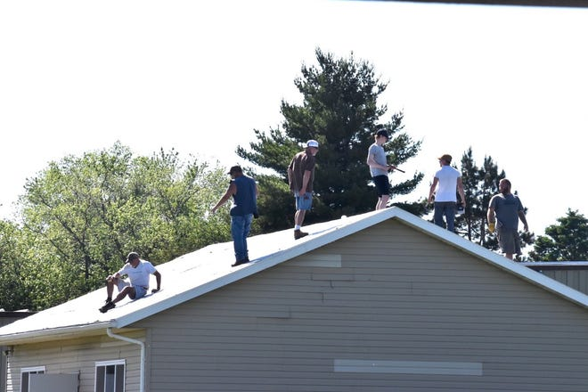 Summer projects for the Orion school district include putting metal roofs on badly damaged athletic buildings at Orion High School. This crew was working on the weight room on Wednesday, May 26.