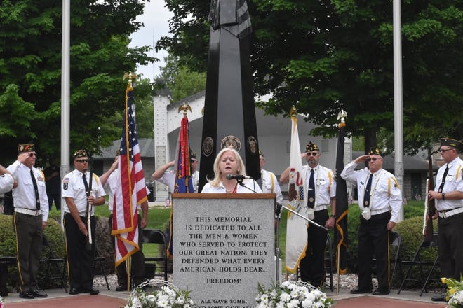 """While the color guard salutes, DeAnne Bloomberg sings """"The Star-Spangled Banner"""" during the Memorial Day observance on Monday, May 31, at the Orion Community Veterans Monument in Central Park."""