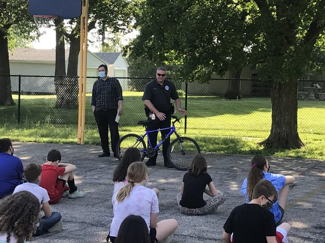 Demonstrating bike safety for the fifth and sixth graders are left Patrick Sloan from the Galva Kiwanis Club and Galva School District officer Ralph Brown, right.